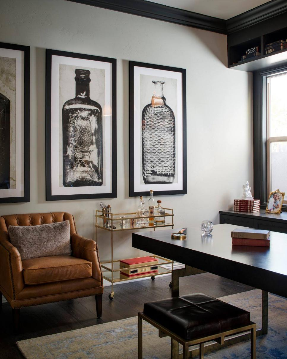 A glass-and-gold bar cart, brown leather armchair and oversized artwork of glass bottles give Mad Men-esque flair to this home