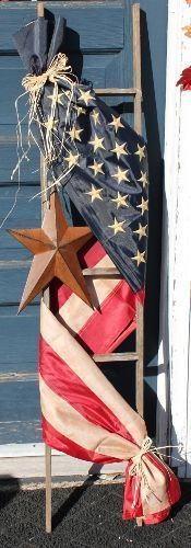 Adorned with a tea-stained Americana flag** and accented with a rusty star and raffia bow, this ladder will be a great addition to
