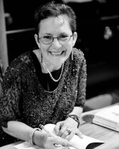 A black and white photo of Amy, a smiling woman with round glasses and a sparkly shirt, writing in a book.