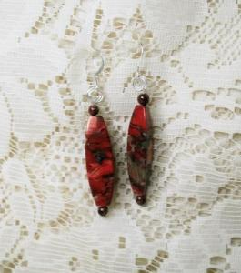 Oblong red and black earrings on a white lace tablecloth.
