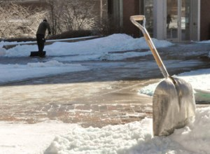 KAT MYERS / The Journal  A Webster staff member works to remove the fallen ice and snow  three days after the storm on Friday, Feb. 4.