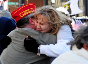 "Kerri German, 47, of Ill., tightly hugs Ron Bartholome, who served in the Marines from 1979-1985, after he yelled, ""Thank you,"" to her from the crowd. BRITTANY RUESS / THE JOURNAL"