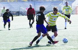 HOLLY SWAN / The Journal Patrick McCaffrey, men's soccer forward, maneuvers around an Iowa Wesleyan defender at a home game on Saturday Nov. 2. Webster defeated Wesleyan 13-0.