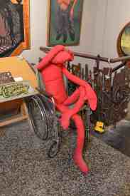 "Jarvis calls the red doll in a wheelchair his ""buddy,"" which accompanies him as he creates his artwork. / photo by Randi Hammor"