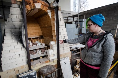 Webster University senior studio arts major Carrie Juenger observes the kiln, which is the oven used to burn or dry pottery and other materials. JORDAN PALMER / The Journal