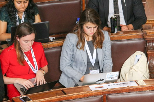 Students Oliviana Bailey (left) and Vesna Ratkovic (right) review amendments on the floor of the Munapest General Assembly in Budapest April 14. BRIAN RUTH / The Journal