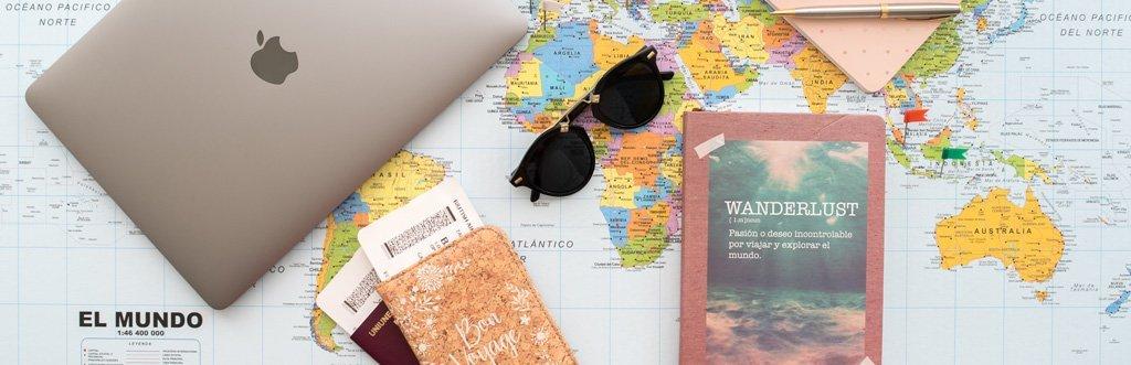 Mapa, pasaporte, macbook, camara foto y gafas de sol recursos para viaje del blog We Collect Postcards