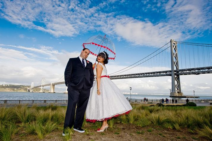 https://i1.wp.com/wedding-pictures-05.onewed.com/14509/retro-bride-white-wedding-dress-red-peticoat-poses-with-groom-near-lake-heart-umbrella-valentines-themed-wedding__full.jpg