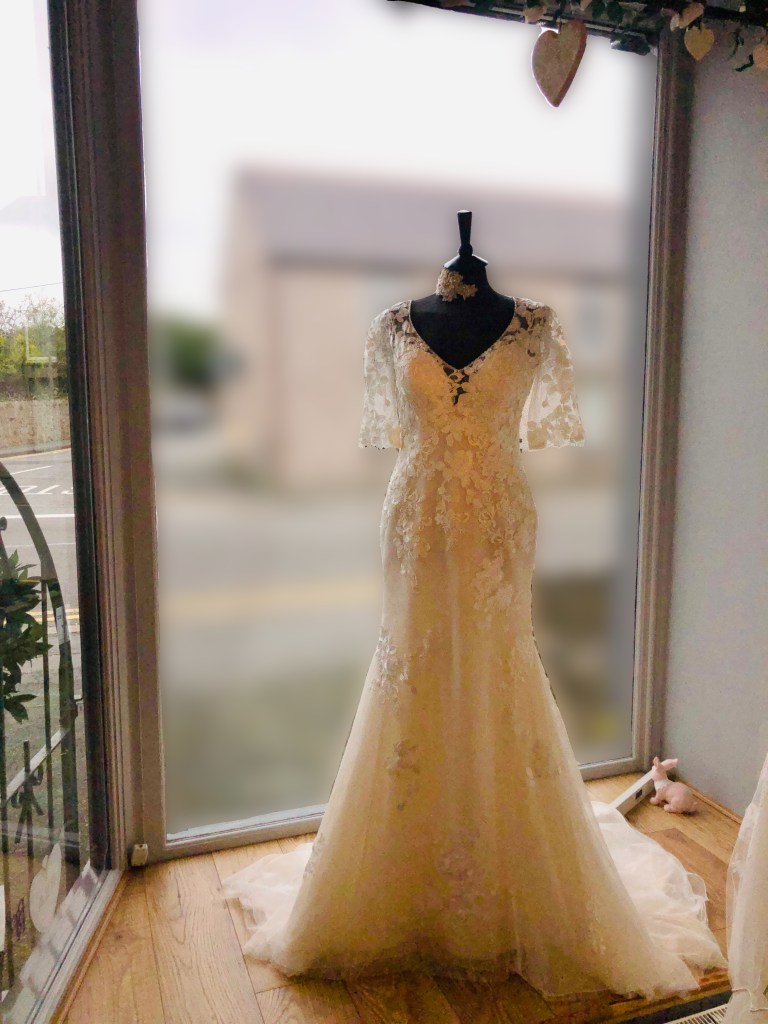 Delicate and enchanting, this allover lace soft fit-and-flare wedding dress features half-length illusion lace sleeves, a V-neckline and V-back subtly lined with beading. Finished with covered buttons over zipper closure. Seen here on a mannequin in Wedding belles window display