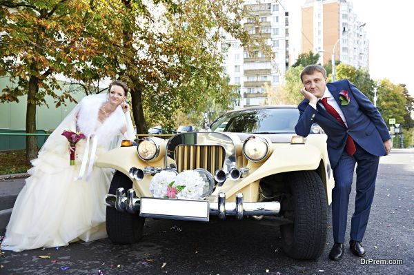 Happy groom and bride about retro limousine