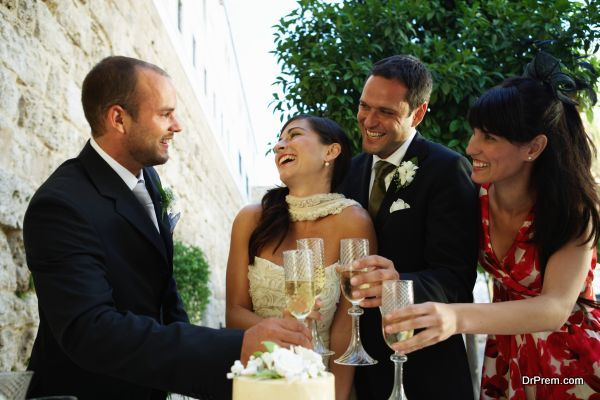 Bride and groom toasting champagne glasses with friends, smiling