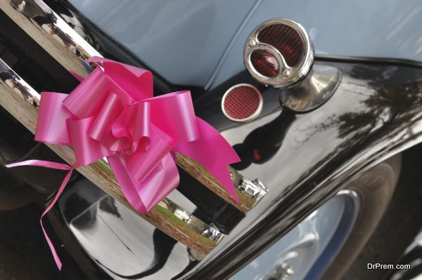 pink ribbon hanging on the back of an old car for a wedding