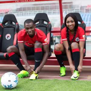 A picture of a footballer and his fiancée dressed in football attire and taken on the pitch