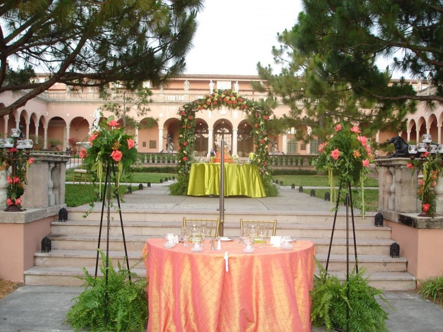 Wedding flowers on tripod and iron arch in the Ringling courtyard