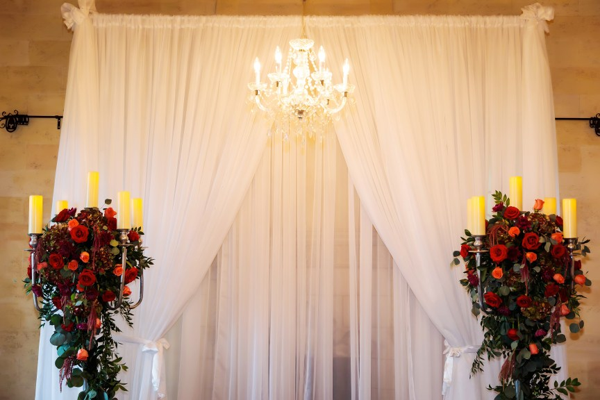 Wedding Ceremony Site with Silver Candelabras with Lush Red and Coral Trailing Flowers