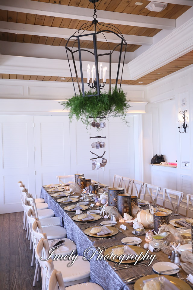 Greens and Hanging Shells on Chandelier Over Feasting Table for Reception