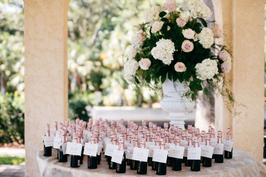 Large Urn of Flowers on Place card table with champagne bottles holding down place cards