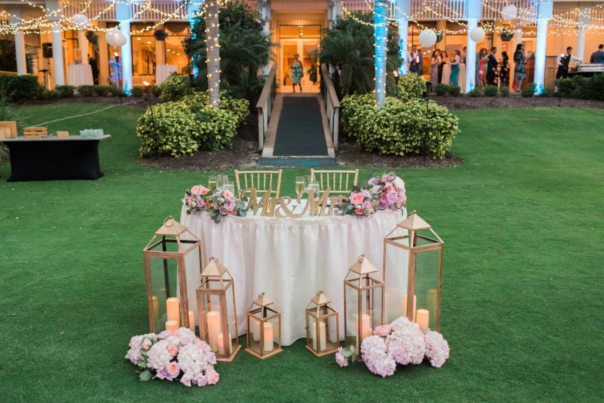 Sweetheart Table with Lanterns and Flowers from Arch