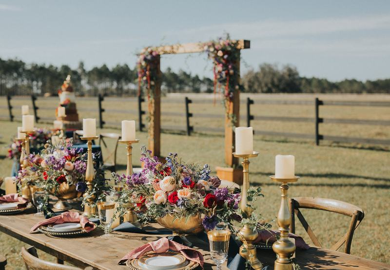 Guest Table with Flowers and Natural Cedar Wedding Arch for Ceremony