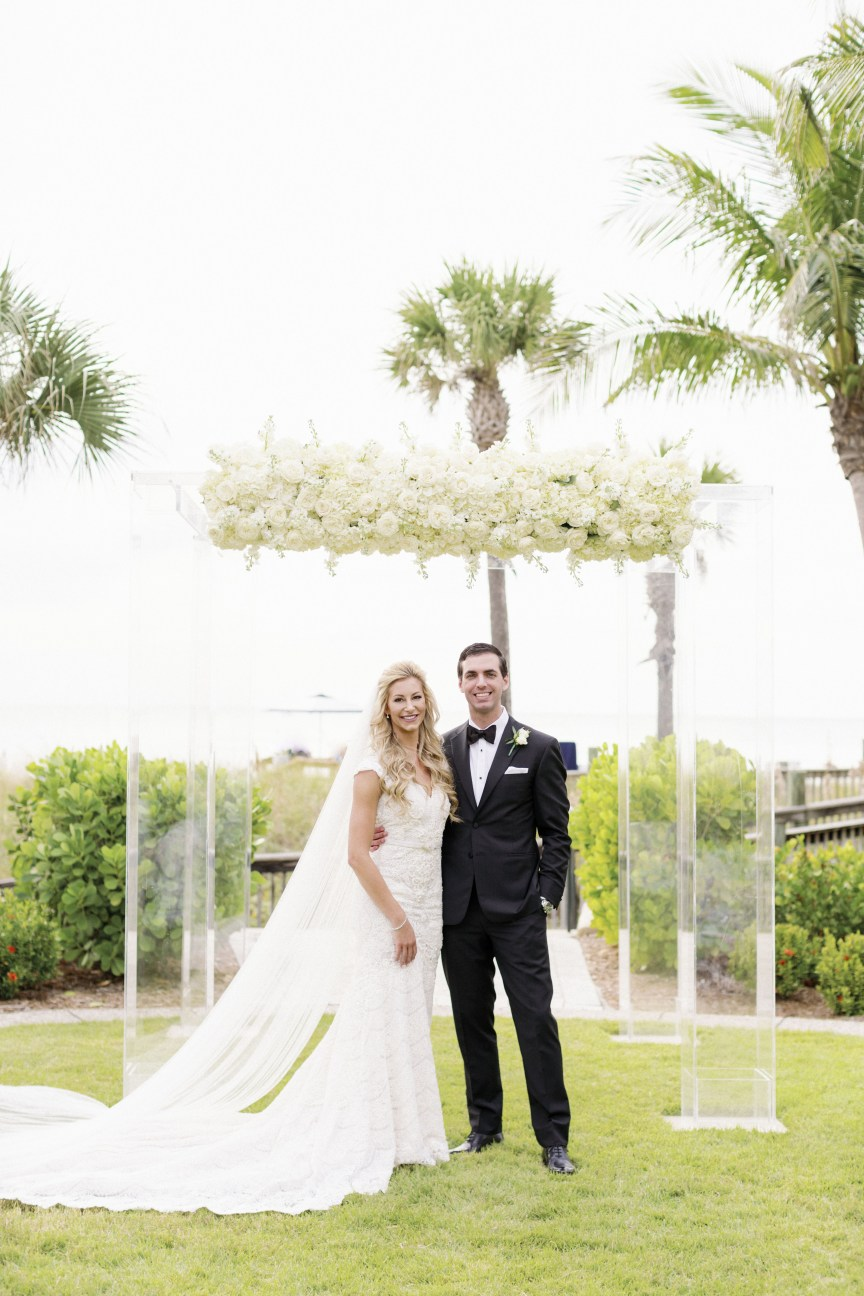 Bride and Groom in front of Acrylic Canopy with All-White Flowers