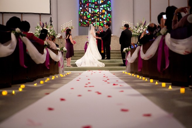 wedding ceremony aisle decorated with aisle runner flower rose petals and candles