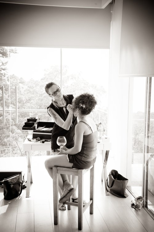 makeup artist applying brides makeup