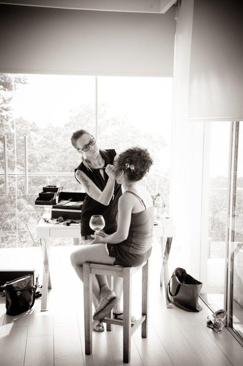 makeup artist applying brides makeup