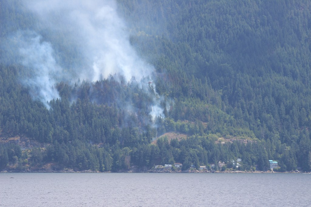 Two helicopters repeatedly drop baskets of water on the forest fire as it threatens the highway and homes