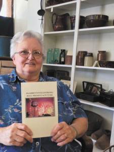 Pam Montgomery holding a copy of her book entitled #GarrettsvilleStrong