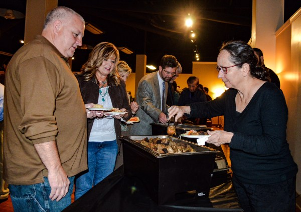 """North Wheeling resident Vera Uyehara prepares to enjoy the catering supplied by the """"Vagabond Chef,"""" Matt Welsch, while Wheeling councilman Don Atkinson and his wife Gail waits their turn."""