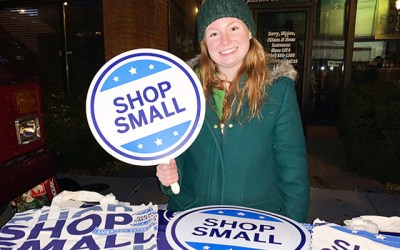 """Valerie holding a """"Shop Small"""" sign"""