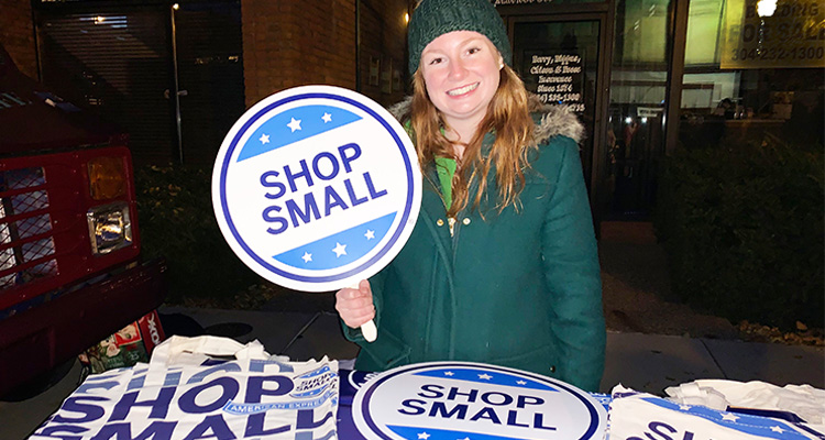 "Valerie holding a ""Shop Small"" sign"