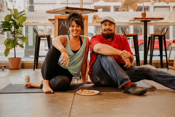 Laura Hitchman and Chef Ryan Butler in yoga poses at The Public Market