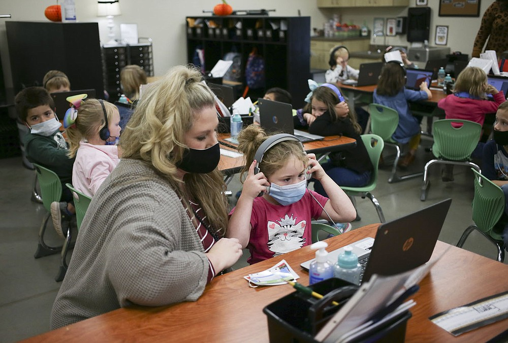 Kim Crawford, kindergarten teacher, (from left) helps Emilea May with an assignment, Monday, October 5, 2020 at Clinton Elementary School in Clinton. Check out nwaonline.com/2010010Daily/ for today's photo gallery.  (NWA Democrat-Gazette/Charlie Kaijo)