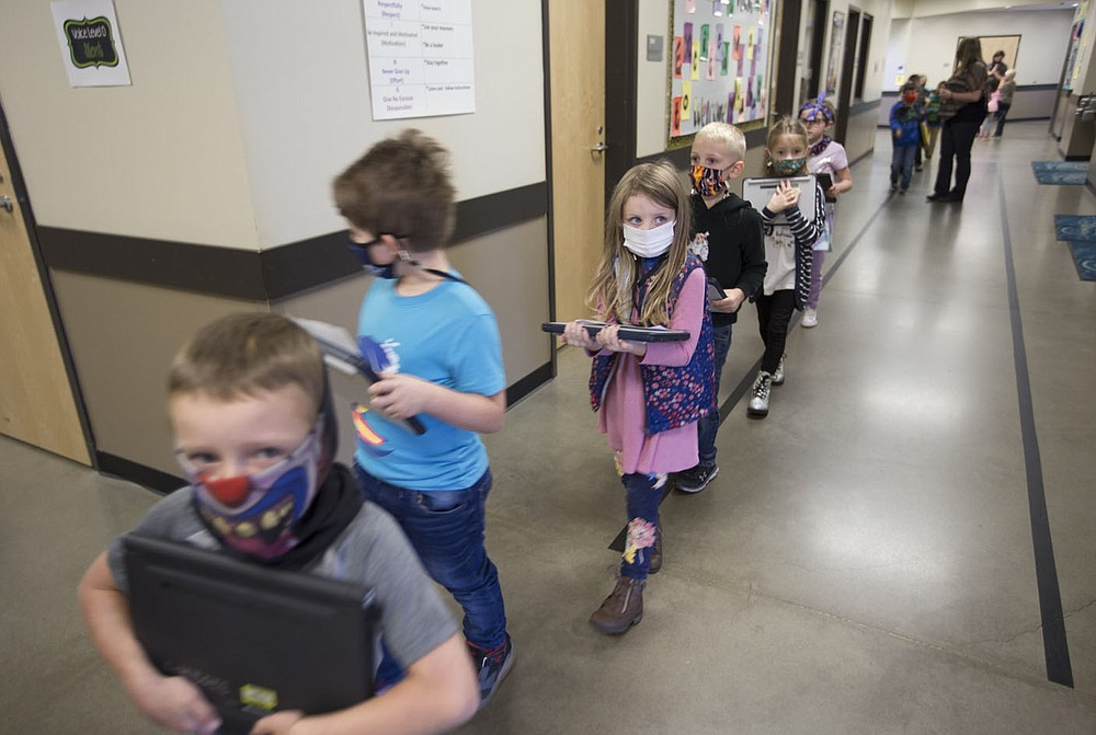 Students cross a hallway, Monday, October 5, 2020 at Clinton Elementary School in Clinton. Check out nwaonline.com/2010010Daily/ for today's photo gallery.  (NWA Democrat-Gazette/Charlie Kaijo)
