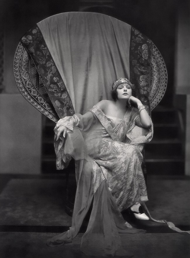 publicity shot of actress Norma Talmadge seated in a large wicker chair.