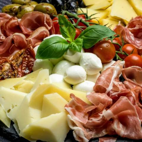 Eine Antipasti-Platte mit Käse, Schinken, Tomaten und Oliven