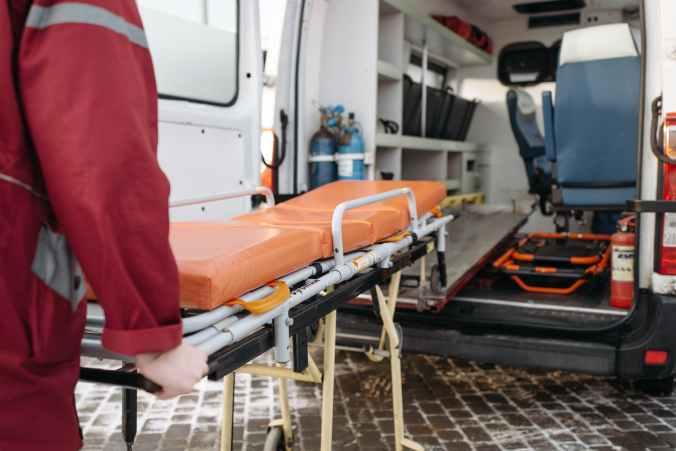 A man pushes a stretcher into an ambulance