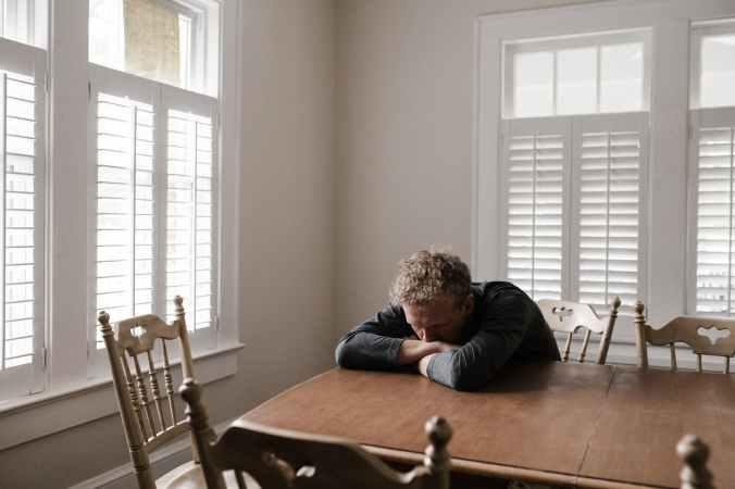 Man sitting down on a chair feeling sad