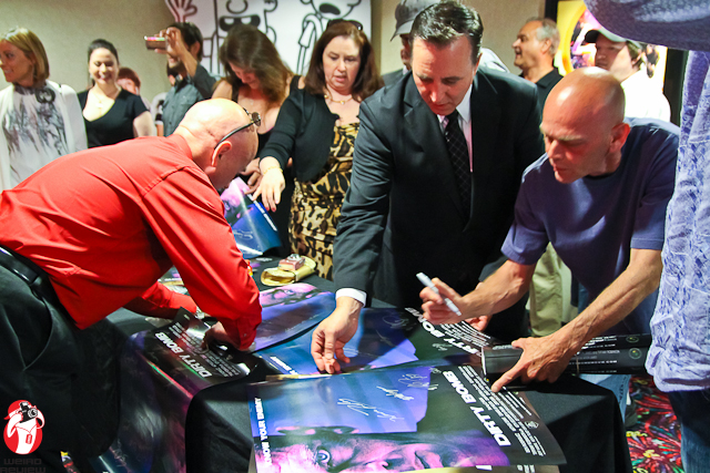 Cast members signing posters for the waiting fans