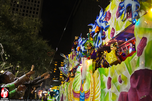 Spectators shout and wave for the attention of the bead laden maskers