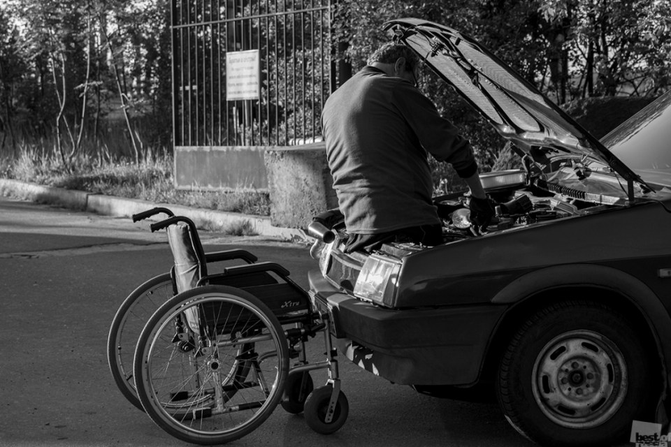 Disabled man fixing his car on the streets of Murmansk. Photo by  Alexey Shchukin