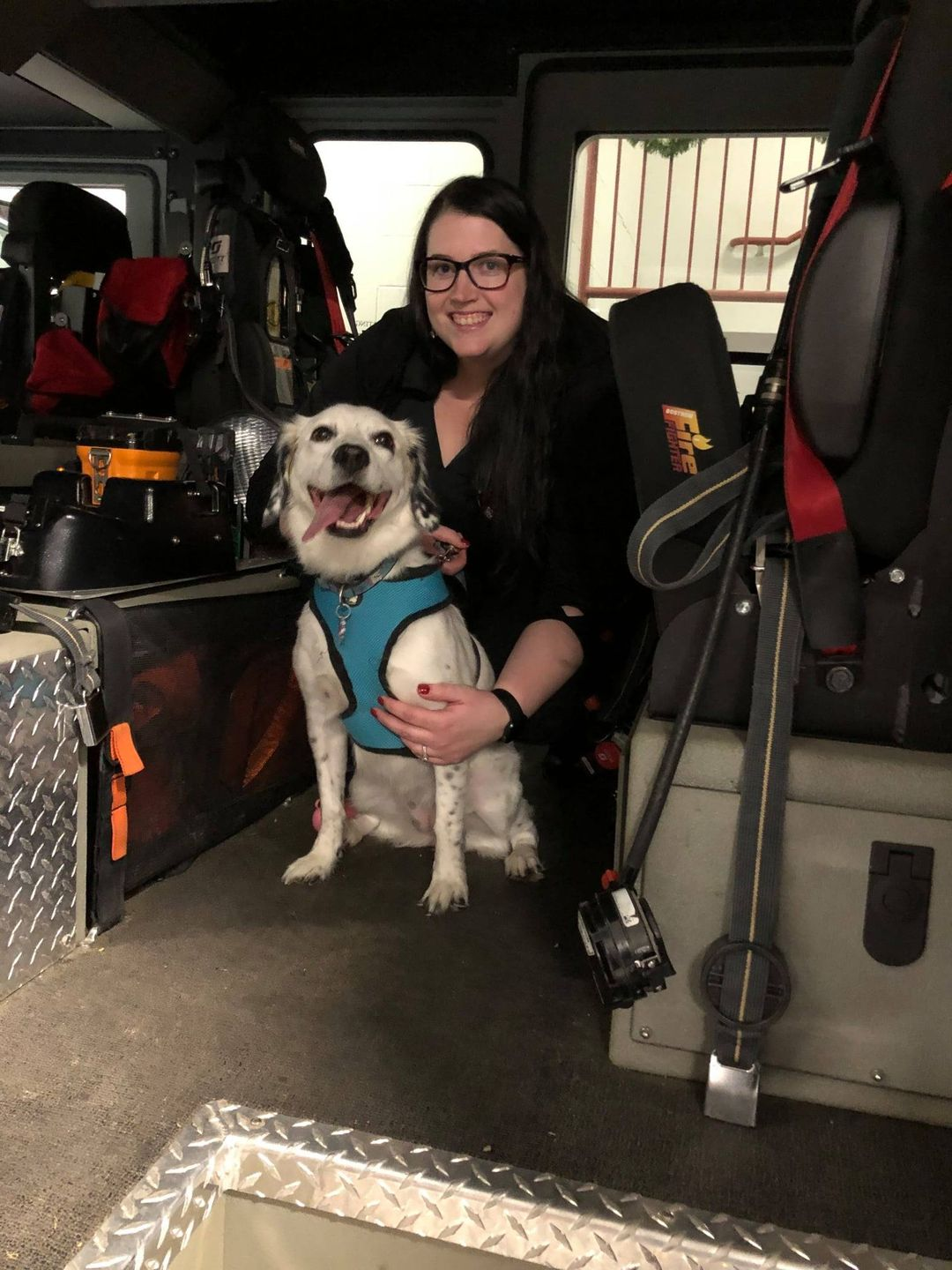 Jackie poses in a fire truck with her dog