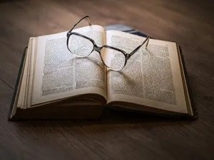 glasses laying on an open book