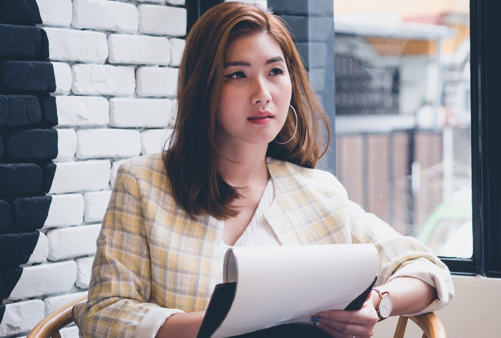 Asian woman working on her paperwork. Young executive concept