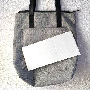 Everlane pocket tote with a piece of cardboard on top of it to place in the bottom of the tote to help it keep its shape
