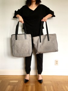 Everlane twill zip tote and pocket tote bags held up side by side for comparison. The pocket tote has a vertical shape with the twill tote has a horizontal shape.