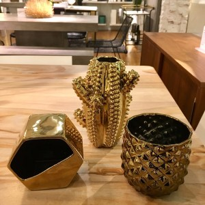 CB2 gold planters. One of them is shaped like a cactus and one of them looks like the bottom half of a pineapple. And there there's one that's hexagon shaped.