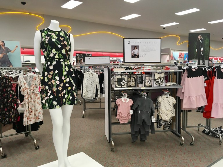 Victoria Beckham for Target, as displayed on launch day. Mannequin wears a floral dress and there are racks of children's clothes behind it.