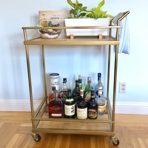 Target threshold bar cart with a whiskey collection on the bottom and plants on top.